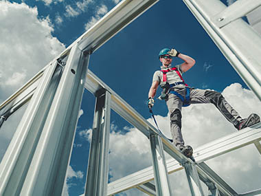 Shock Absorbing Lanyard and Safety Harness Equipment. Work at Height Safety. Caucasian Contractor on a Steel Building Frame.